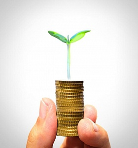 Businessman-holding-plant-sprouting-from-a-handful-of-golden-coi