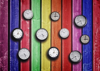 Clocks-on-colorful-wood-background--time-concept