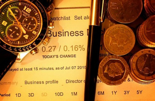 Money-with-pen-and-watch-on-financial-data--finance-concept